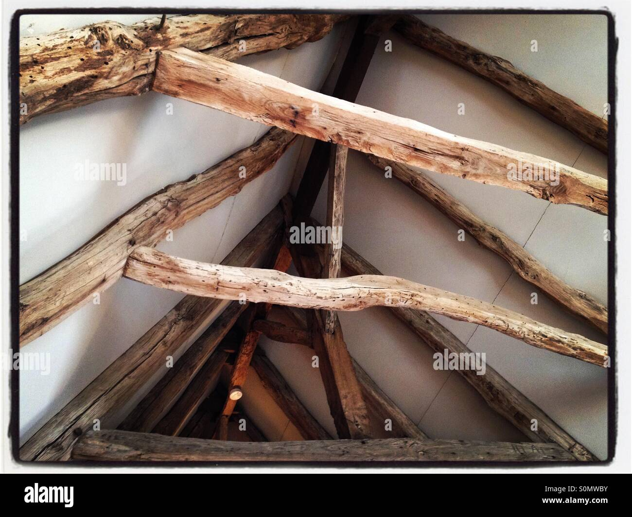 Old wooden roof timbers exposed after a house restoration - Stock Image