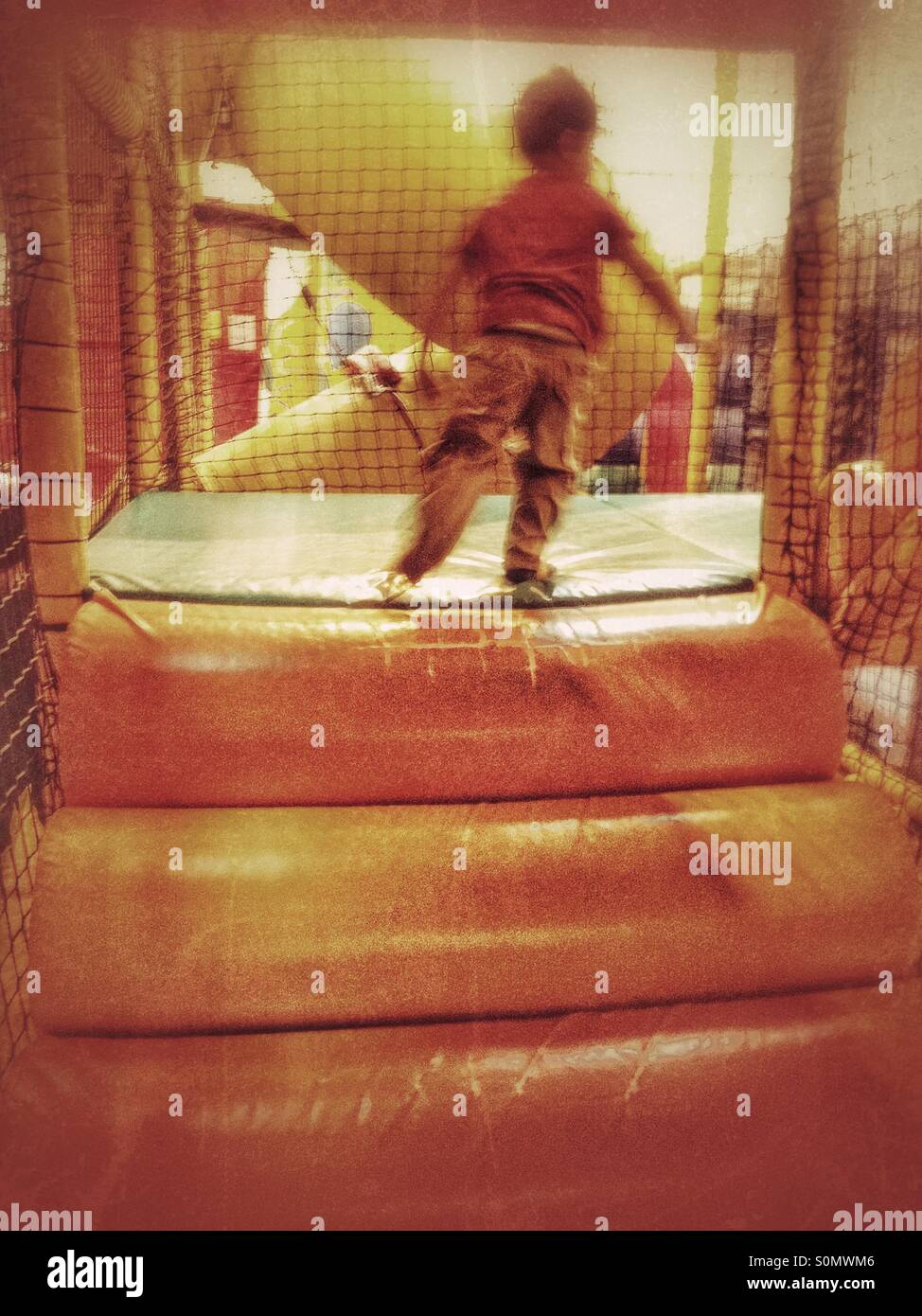 Young boy having fun at a soft play place. - Stock Image