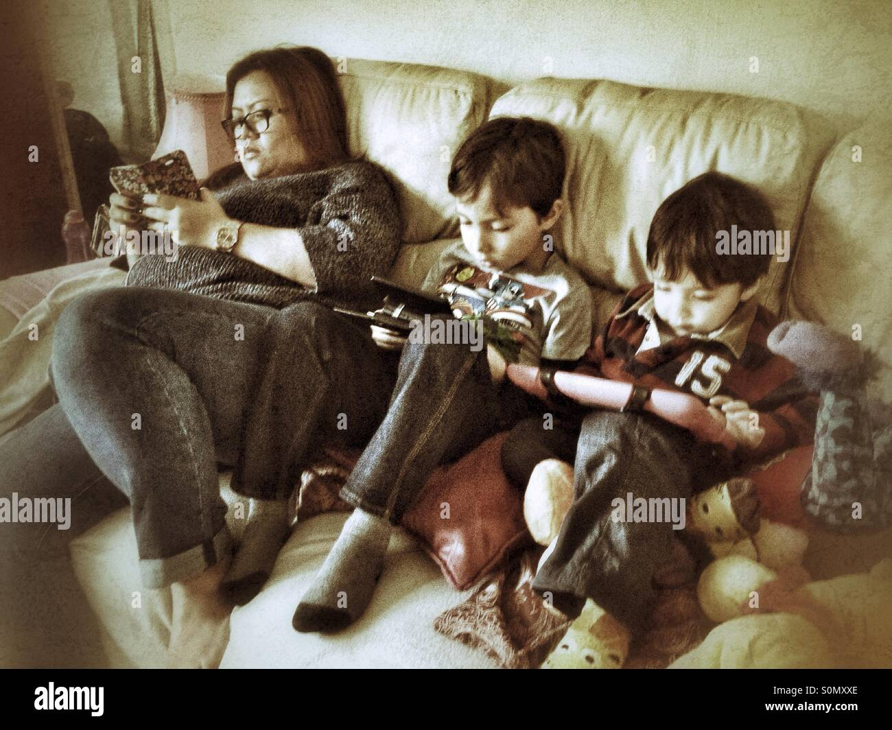 Family using gadgets on the sofa. - Stock Image