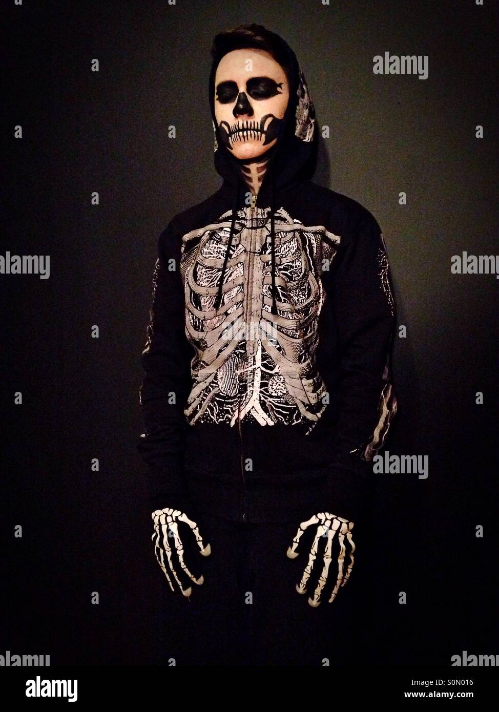 A person dressed as a skeleton. - Stock Image