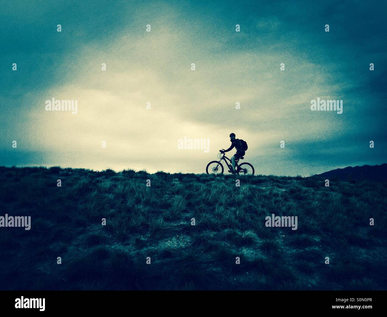 The silhouette of a man riding a mountain bike up the hill in northern Utah. - Stock Image