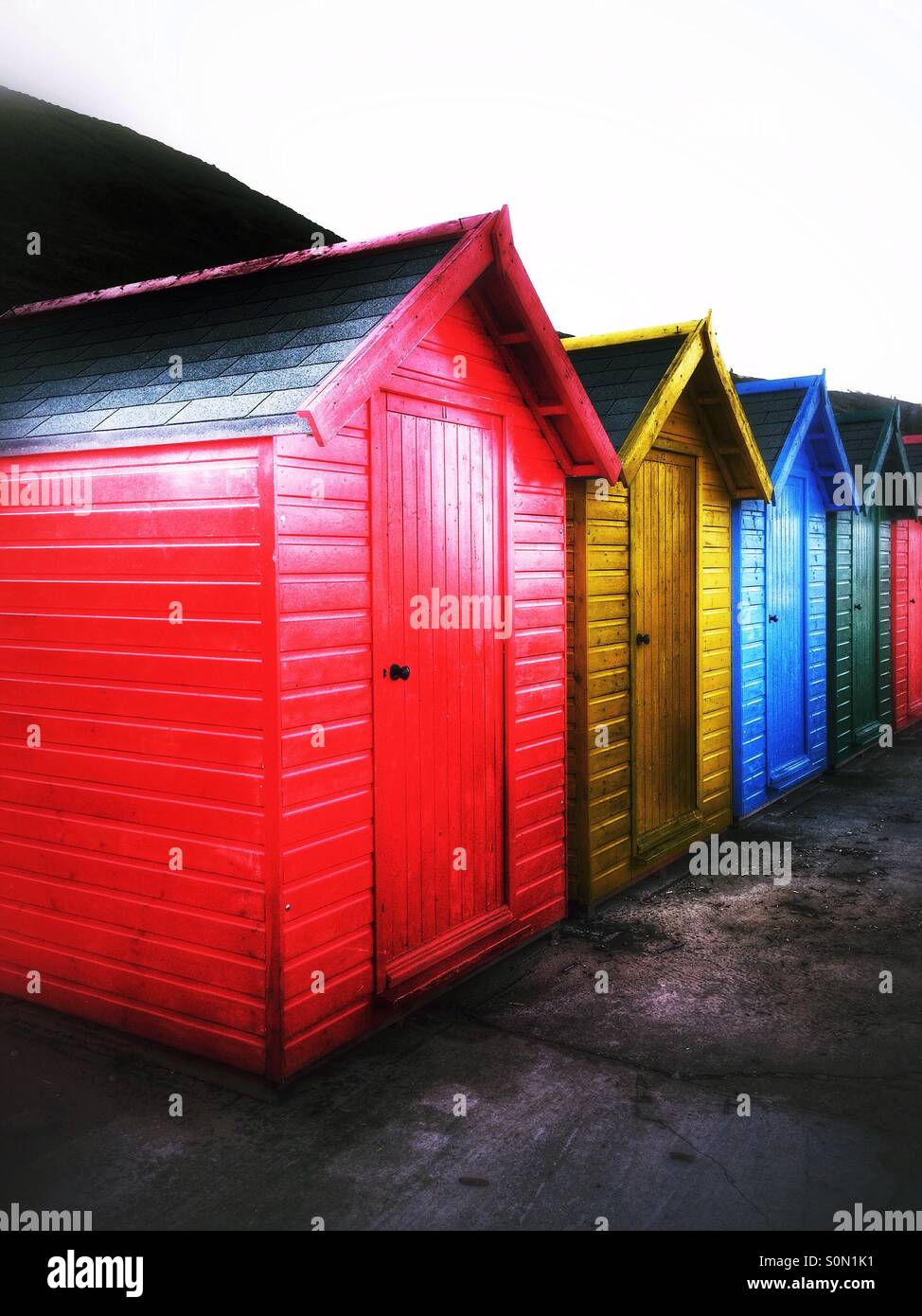 Colourfully painted beach huts at Whitby North Yorkshire England UK - Stock Image