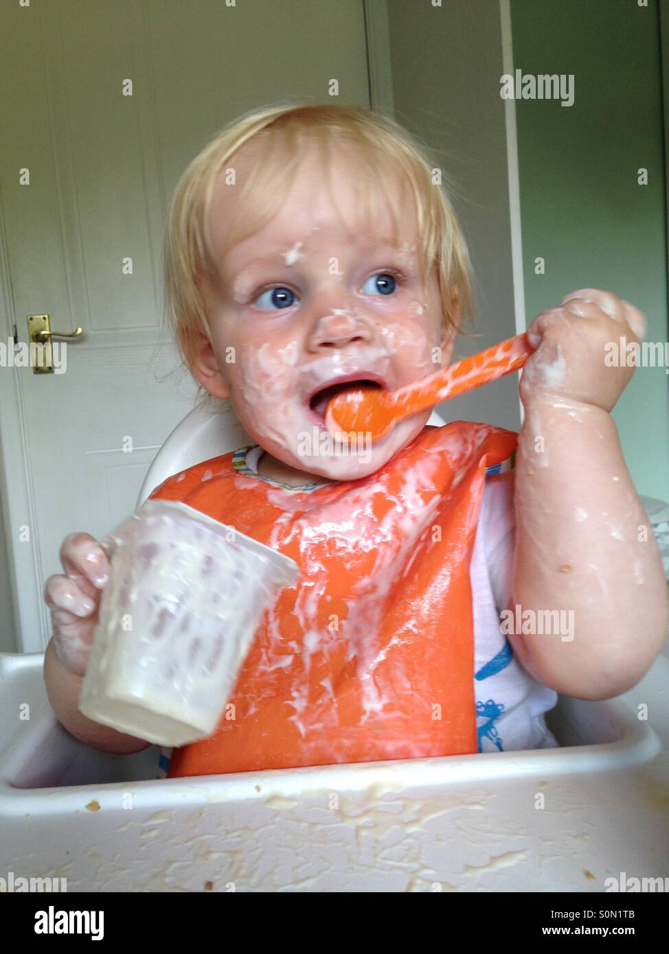 Baby making a mess eating a yoghurt - Stock Image