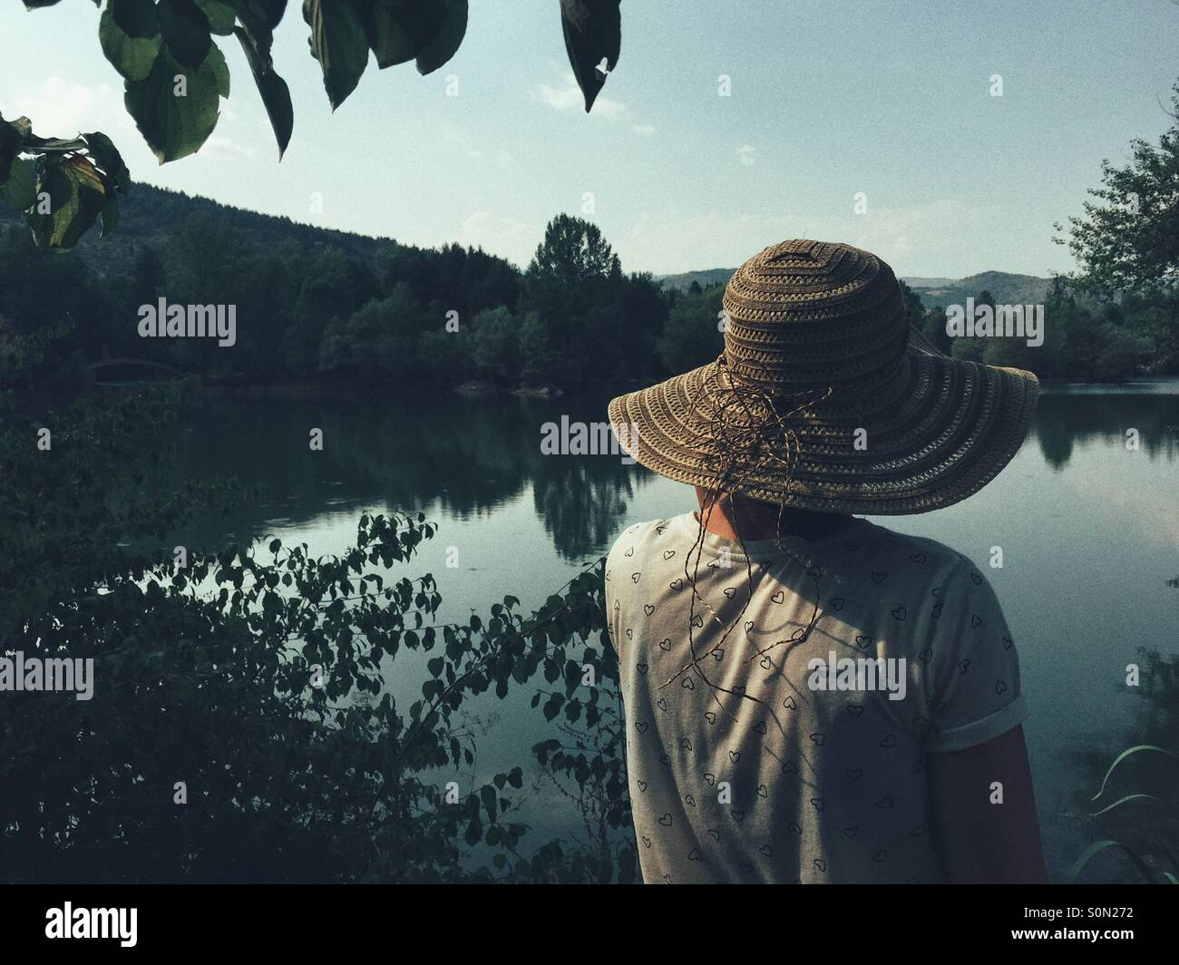 Rear view of Woman looking across lake - Stock Image