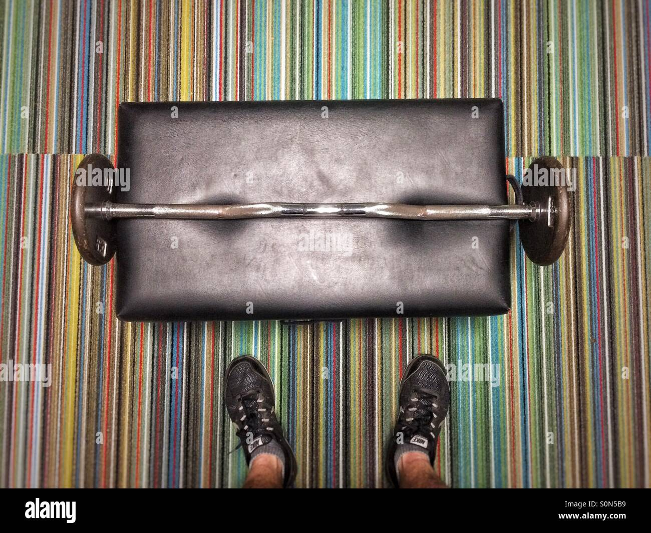 Man before barbell at gym - Stock Image