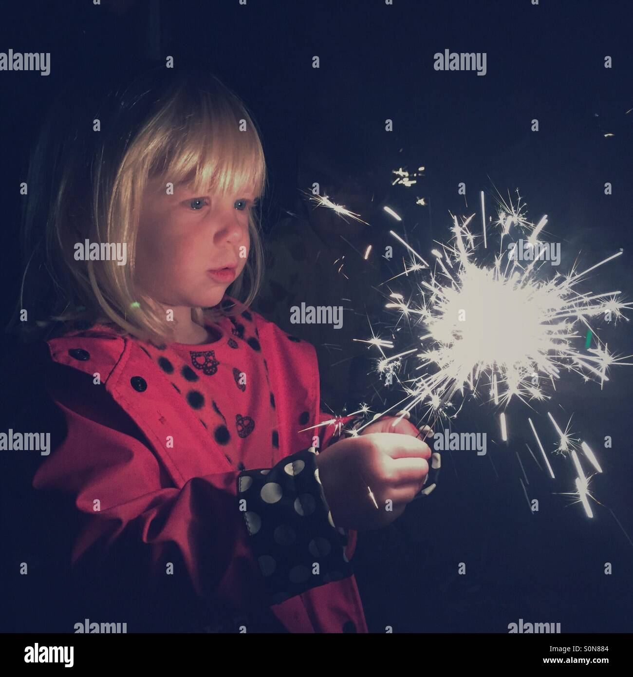 Young blonde Caucasian girl stares intently as a sparkler she is holding illuminates her face. - Stock Image