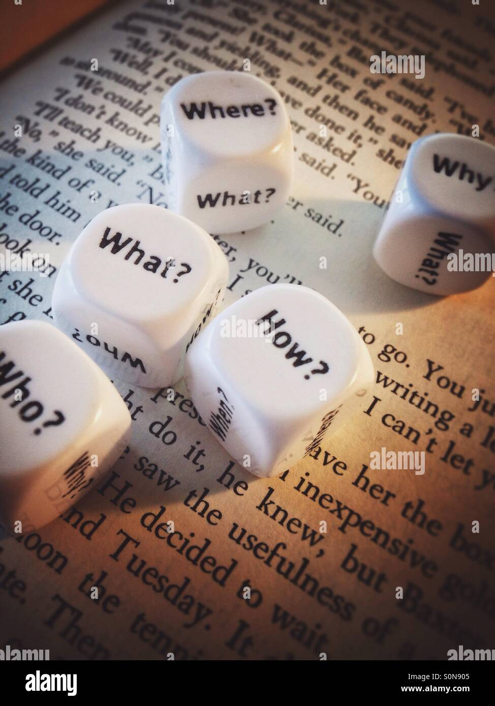 A couple of dice with question words on the page of an open book - Stock Image