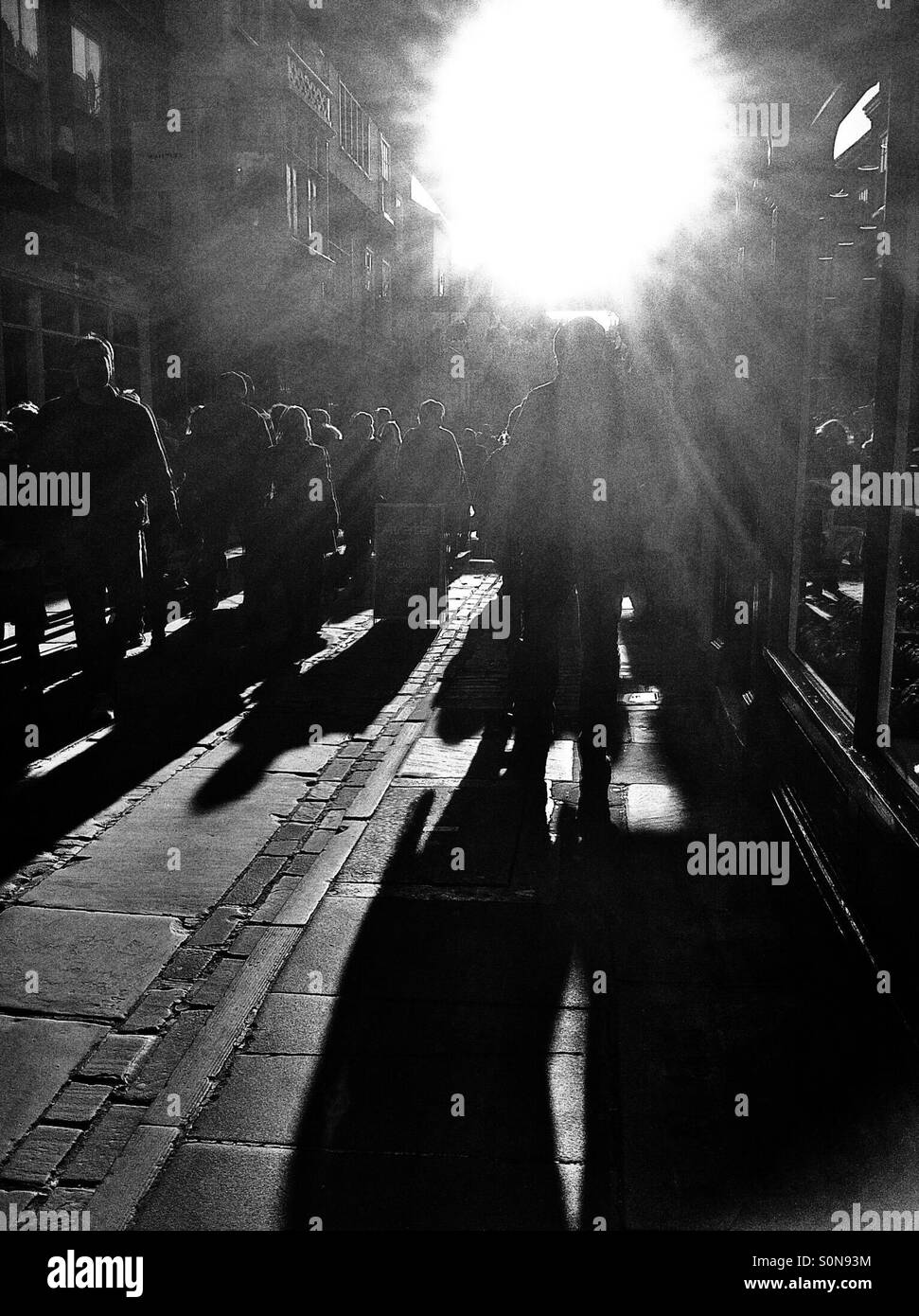Silhouettes of people walking along cobbled street England UK - Stock Image