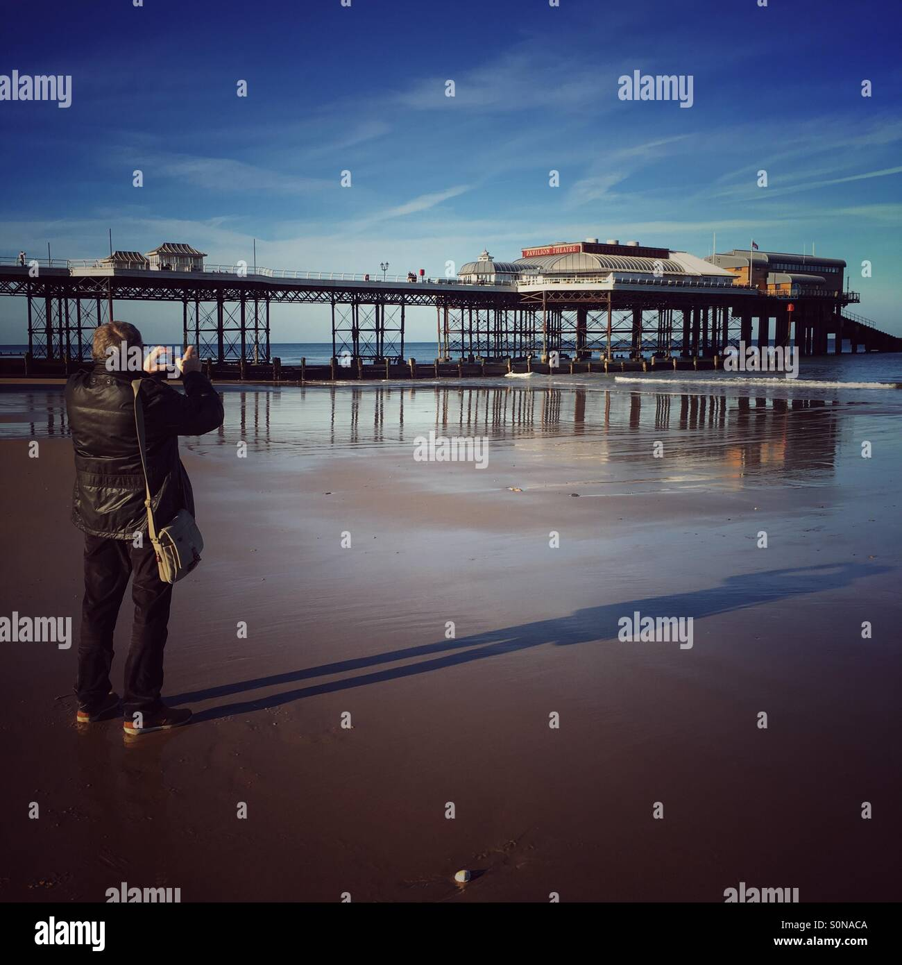 A gentleman taking a photo of Cromer Pier in Norfolk - Stock Image