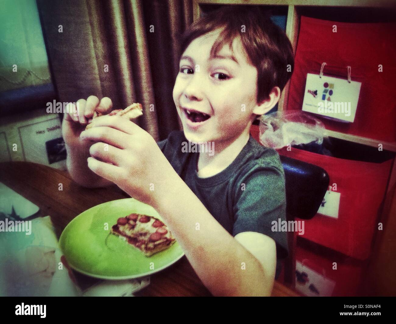 Young boy eating toast. - Stock Image