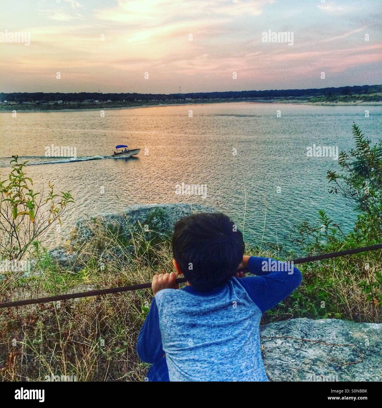 Boy watches the boats pass by - Stock Image