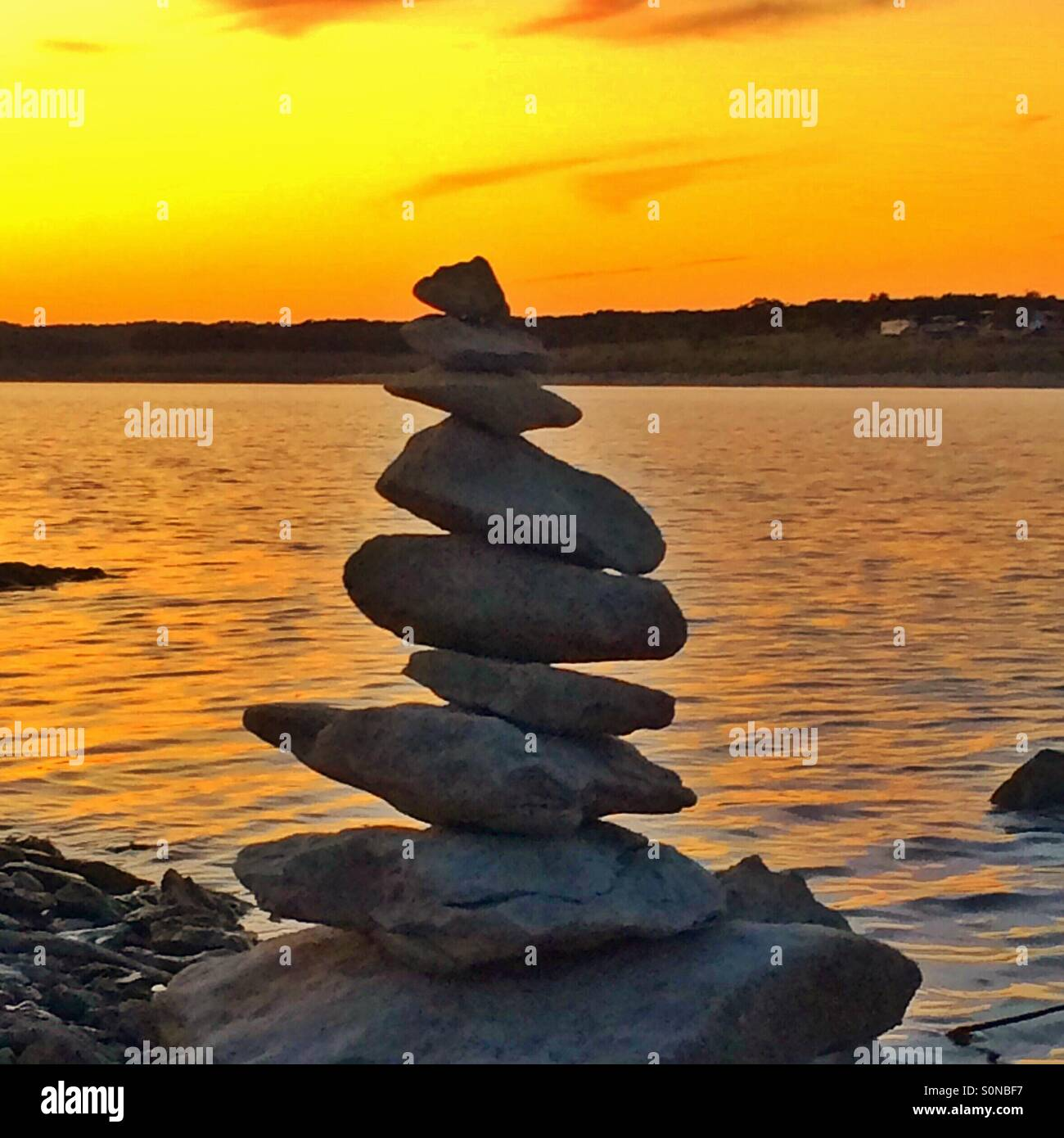 Stacked rocks at water's edge - Stock Image