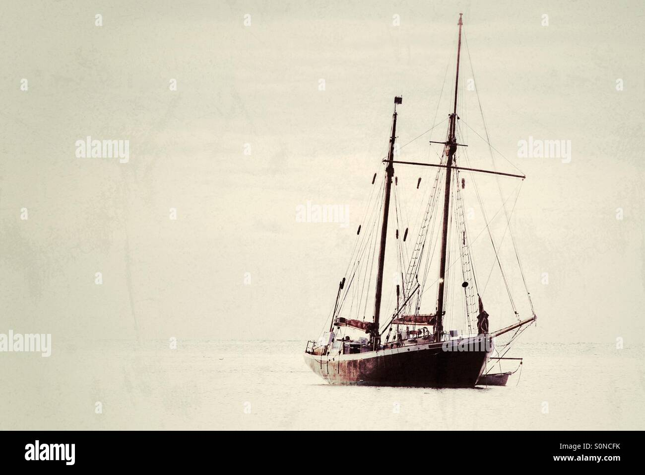 A single, twin masted yacht floating on a calm, flat Ocean. Stock Photo