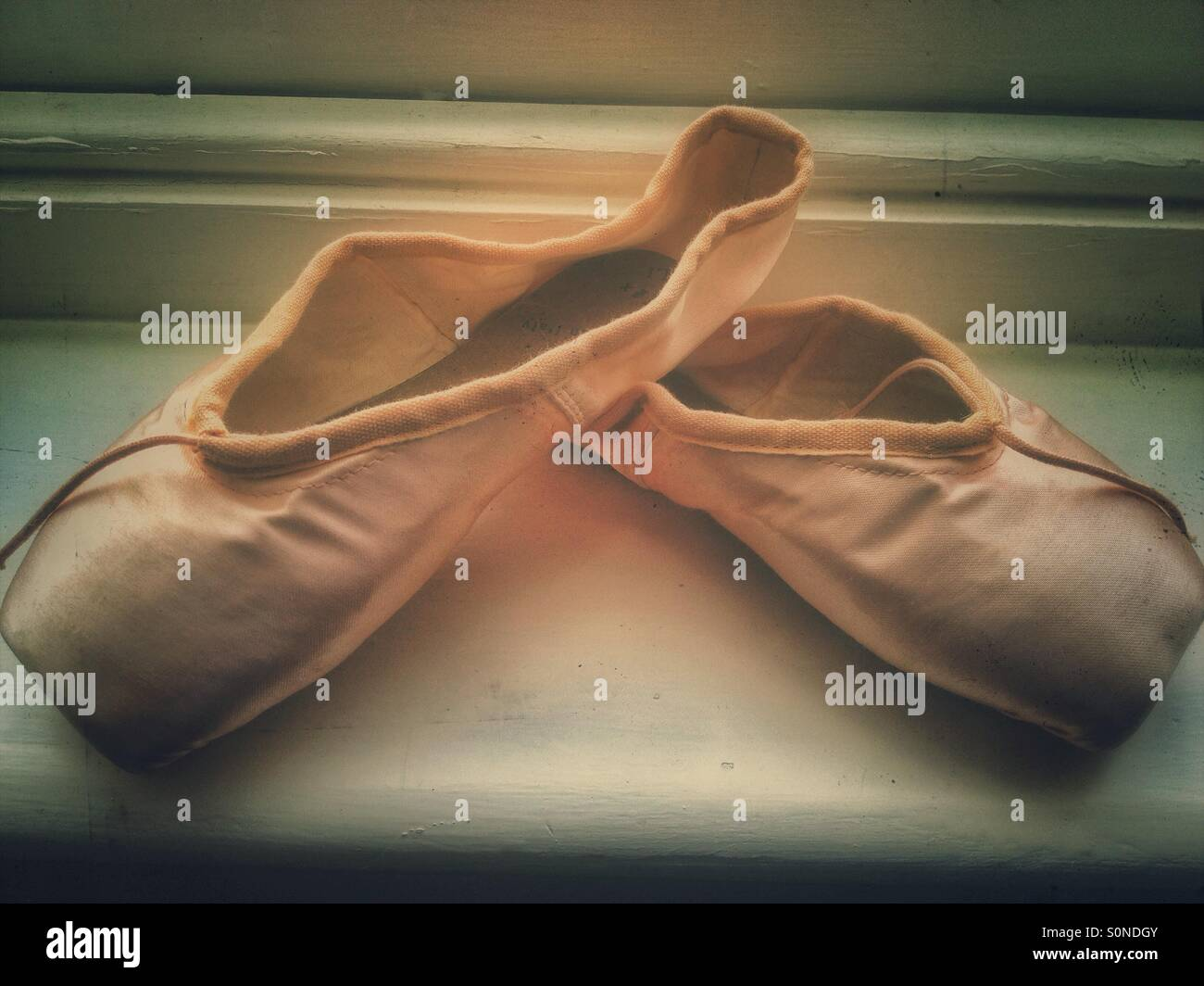 A pair of people no ballet shoes on a window sill. - Stock Image