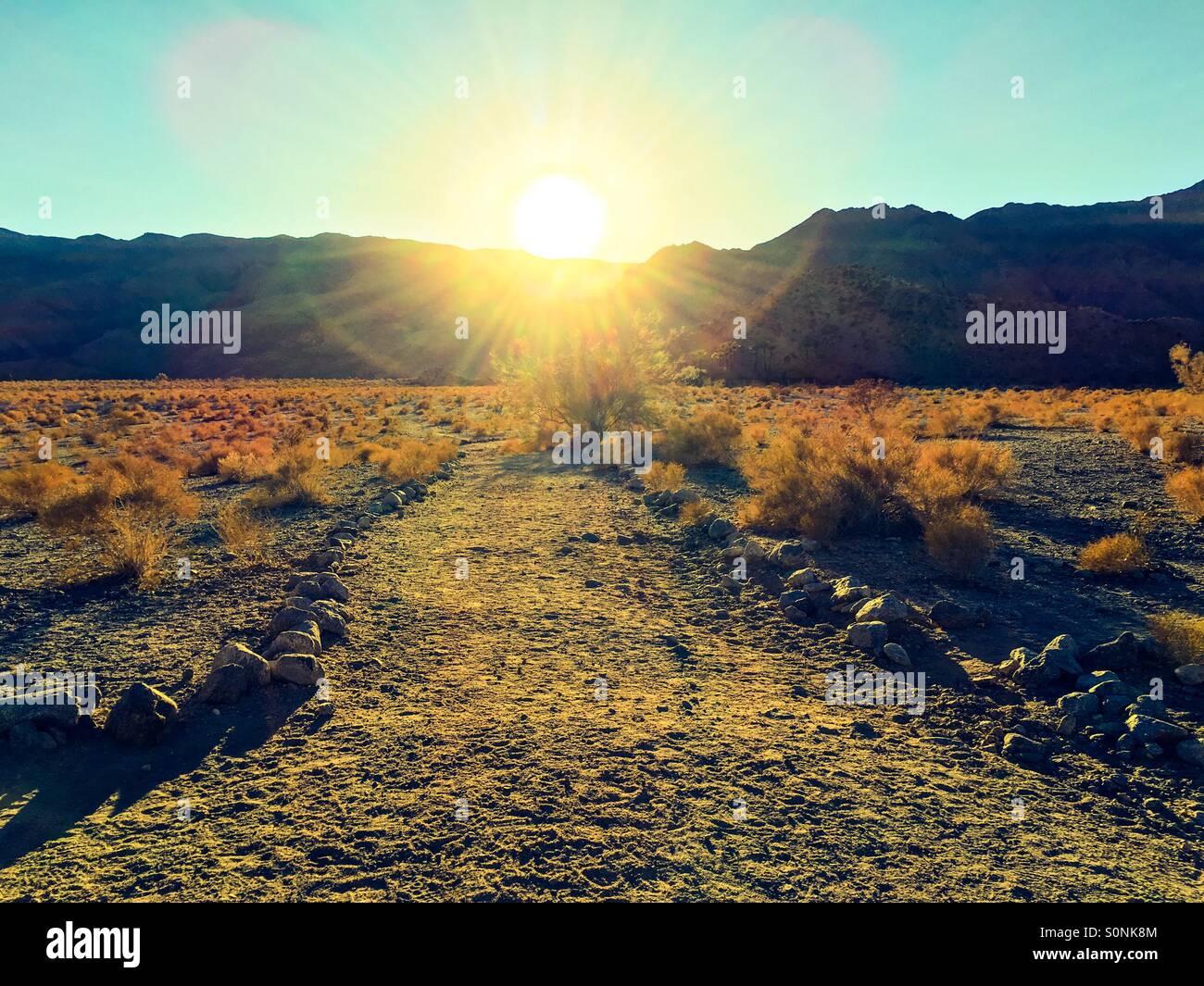 The sun sets behind the Santa Rosa Mountains behind La Quinta, California - Stock Image