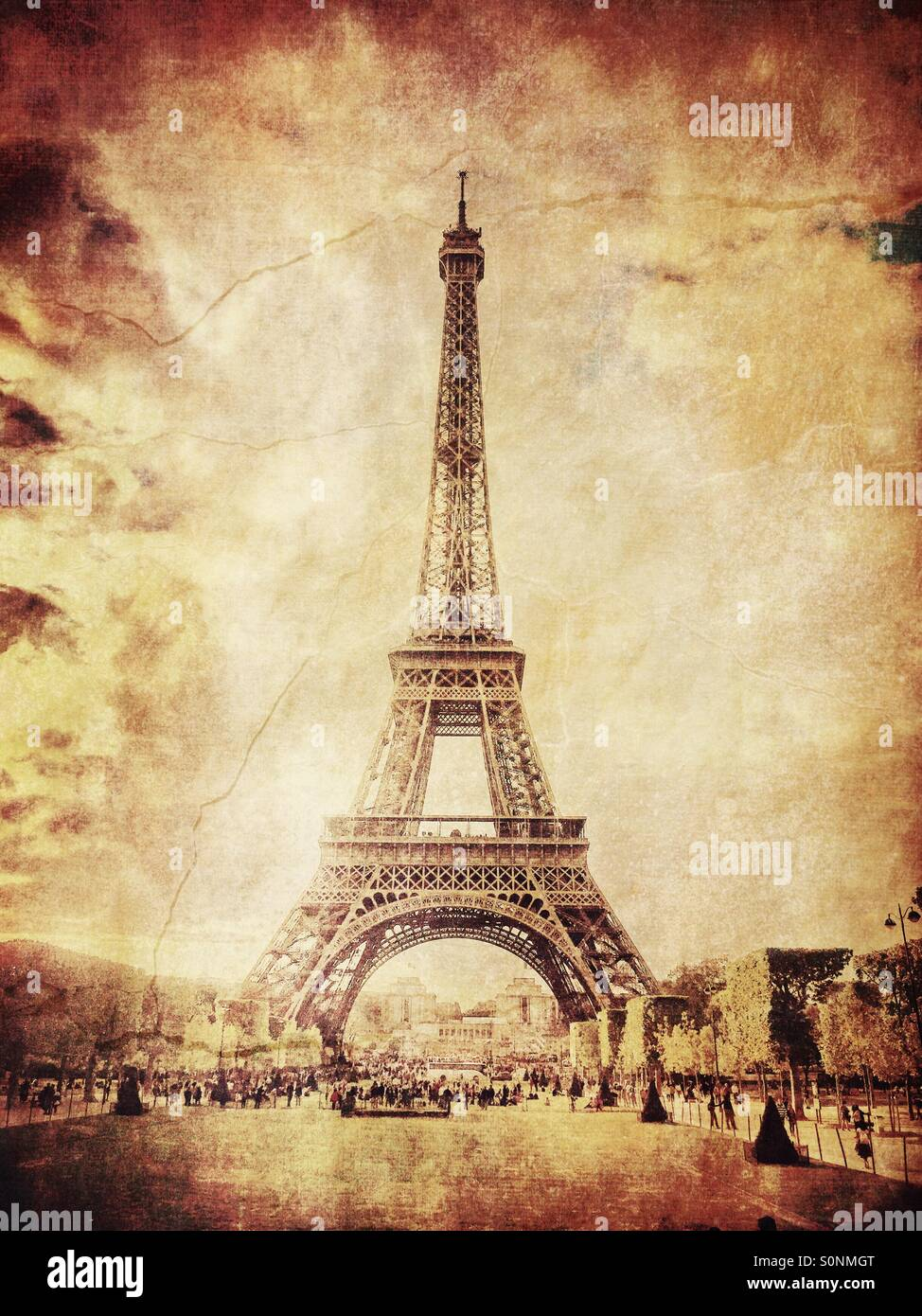 View of Eiffel Tower from Champs de Mars in Paris, France. Aged sepia tones and vintage paper texture overlay.Stock Photo