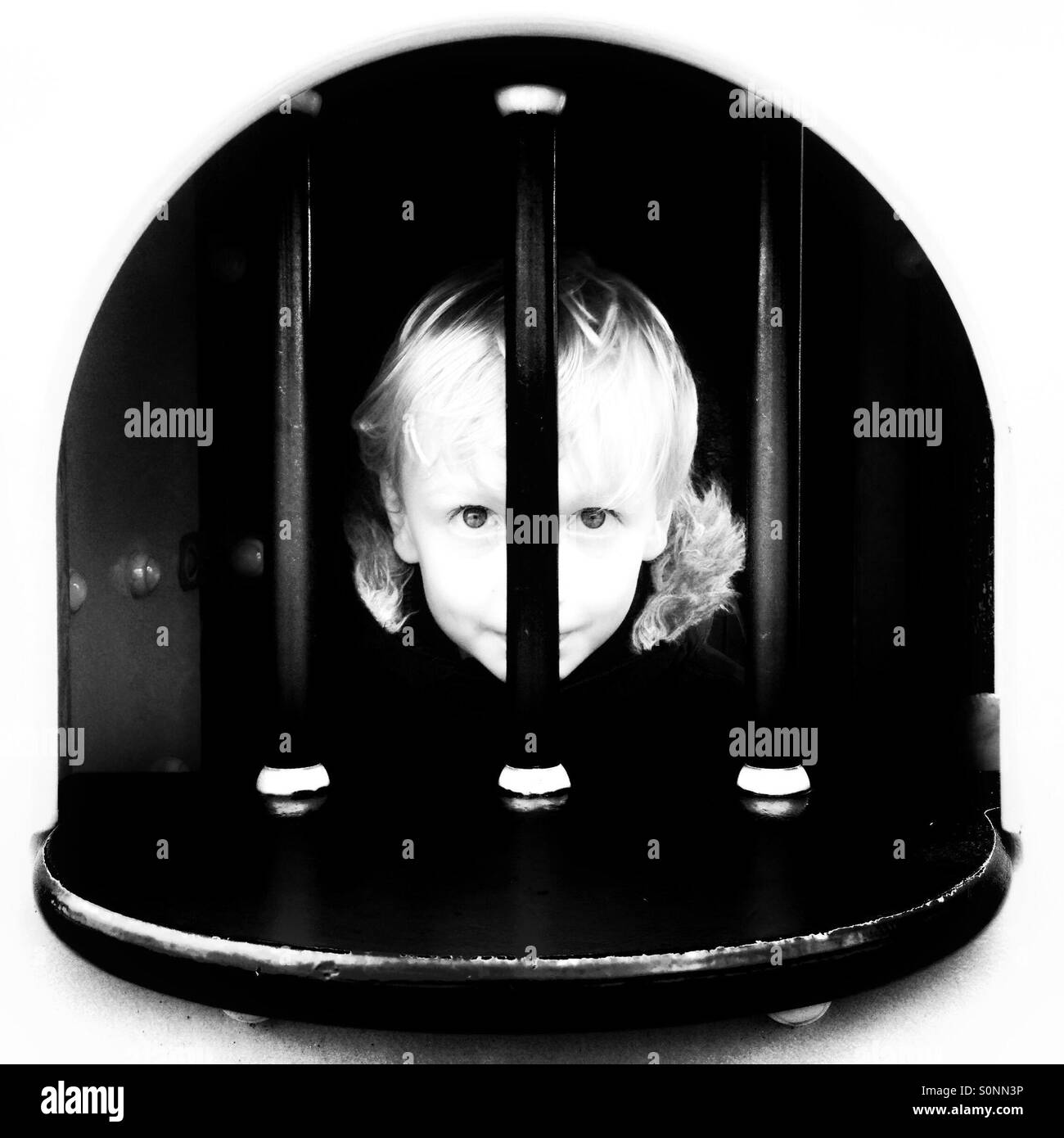 Boy looking through bars in black and white - Stock Image