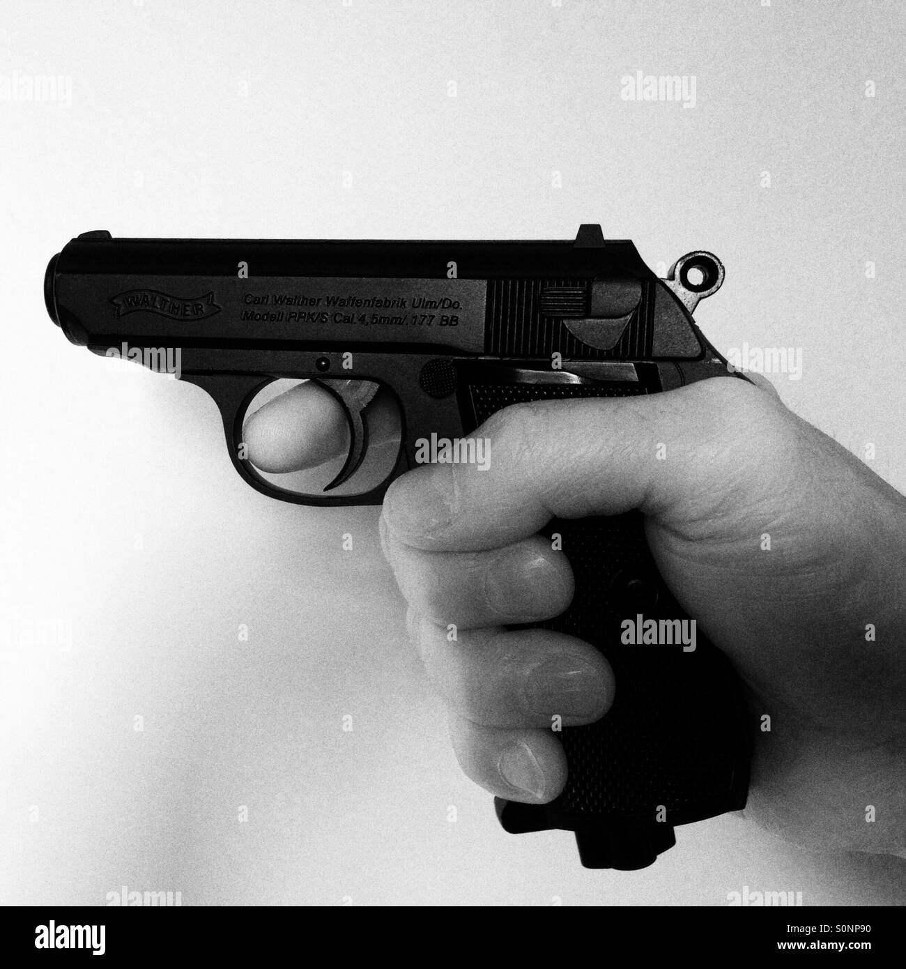 Walther PPK pistol finger on the trigger Stock Photo