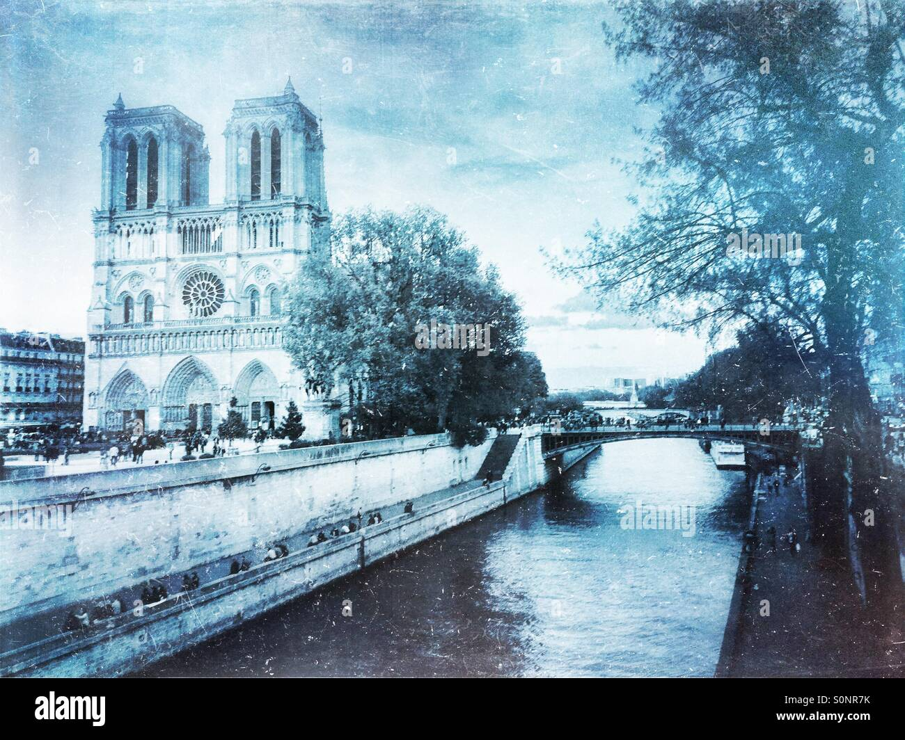 View of Notre Dame Cathedral from Petit Pont across the Seine River. Frosty, winter-inspired vintage paper texture Stock Photo