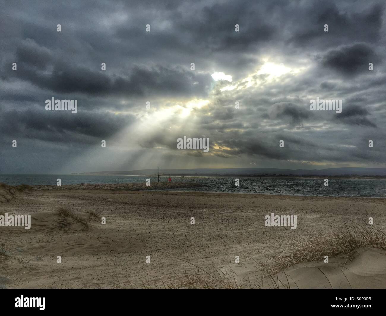 Sun beams over sea on Dorset beach in winter - Stock Image