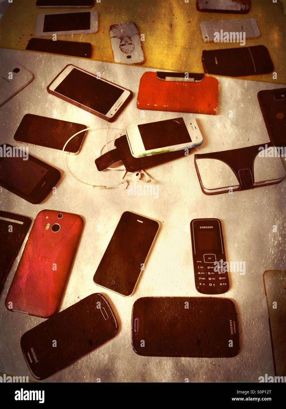 Smartphones and cellphones on a table during an exam to prevent cheating - Stock Image