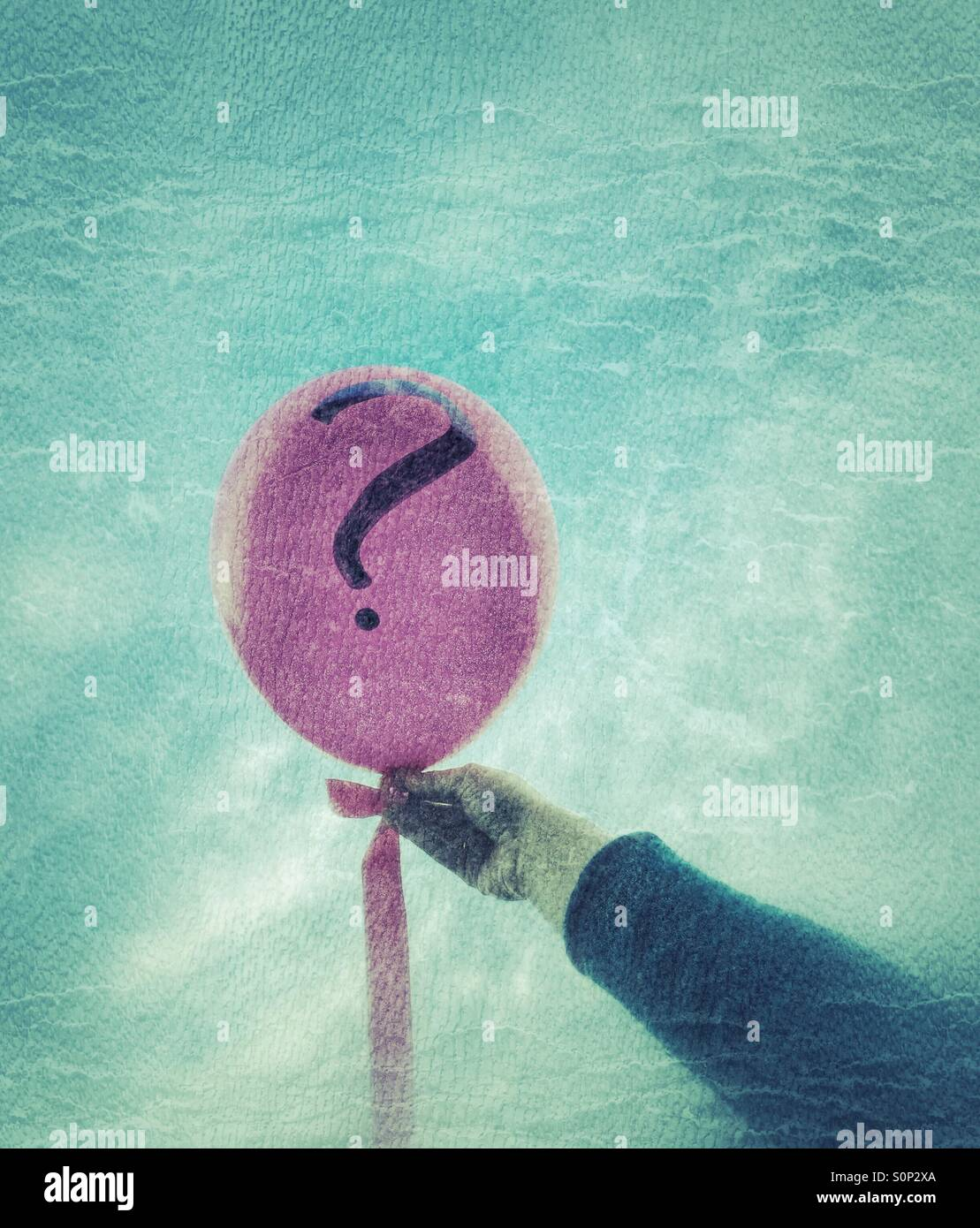 A woman holding a balloon with a question mark. - Stock Image