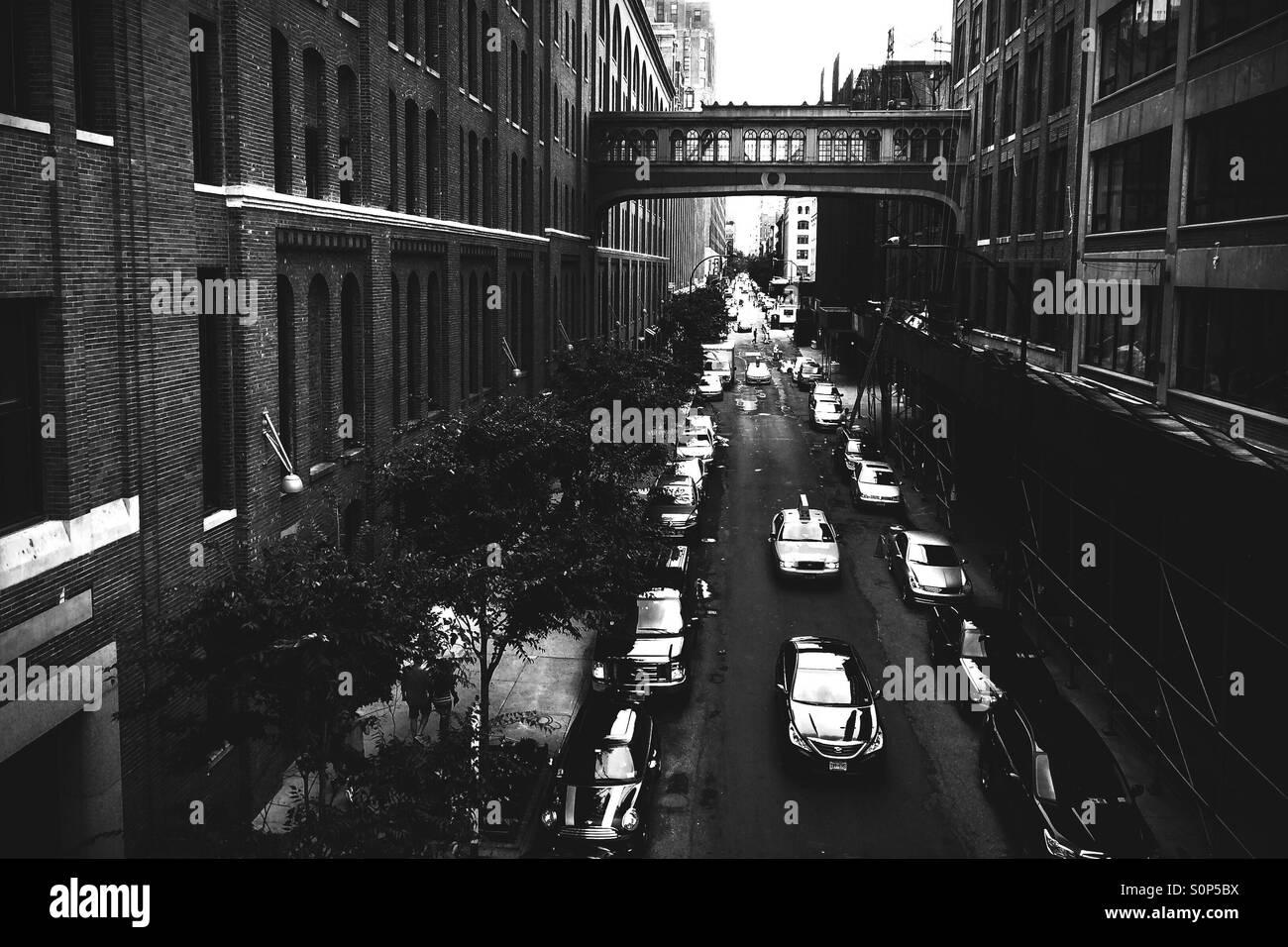 Cars travel beneath a New York City skybridge - Stock Image