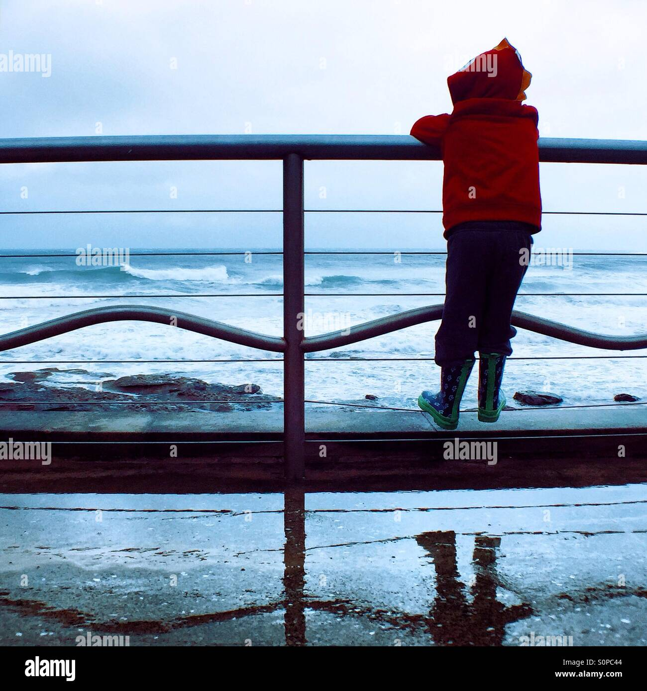 Boy looking at the ocean. - Stock Image