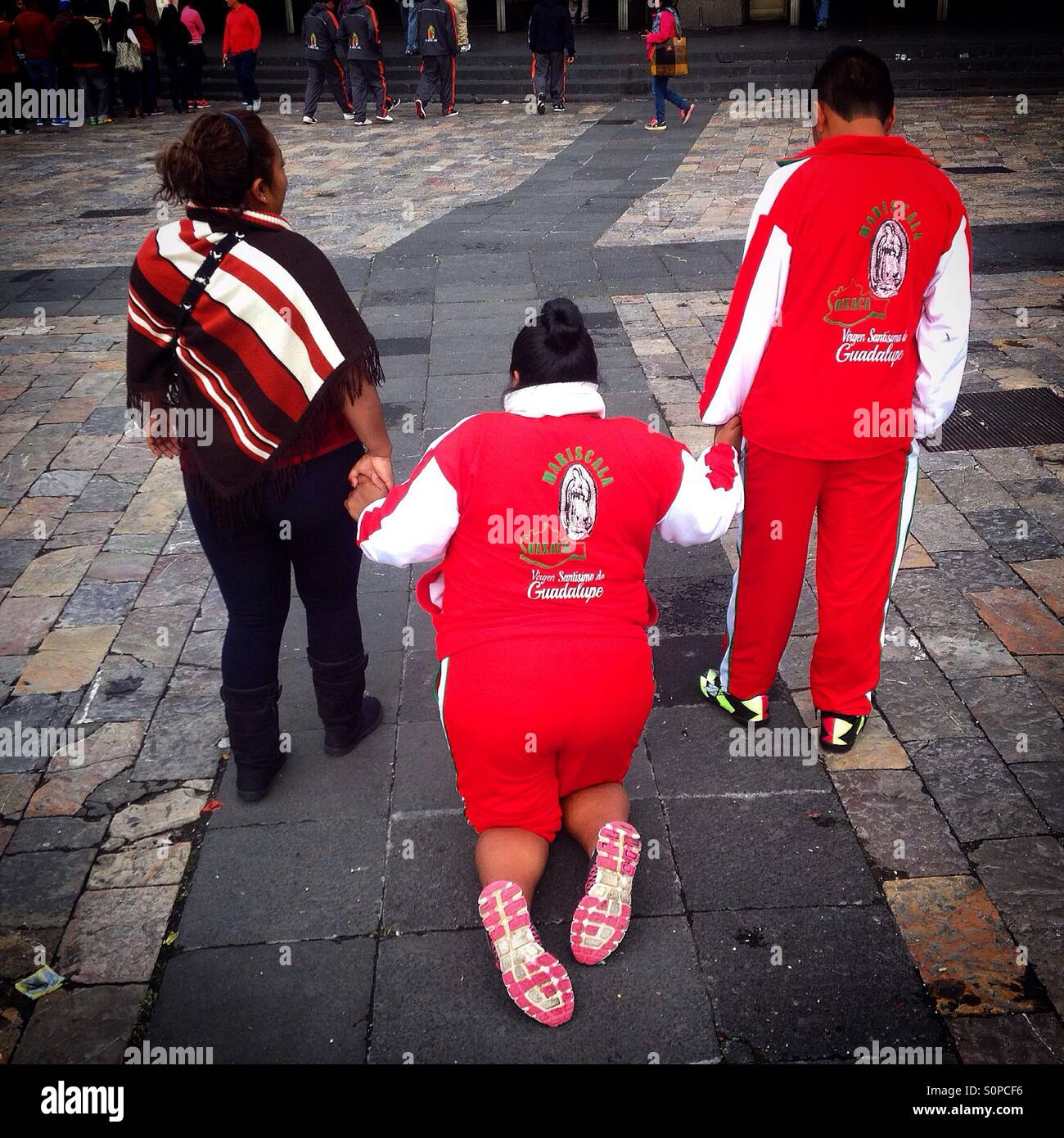 Pilgrims help a woman walking in her knees during the pilgrimage to the Basilica of Our Lady of Guadalupe, Mexico - Stock Image