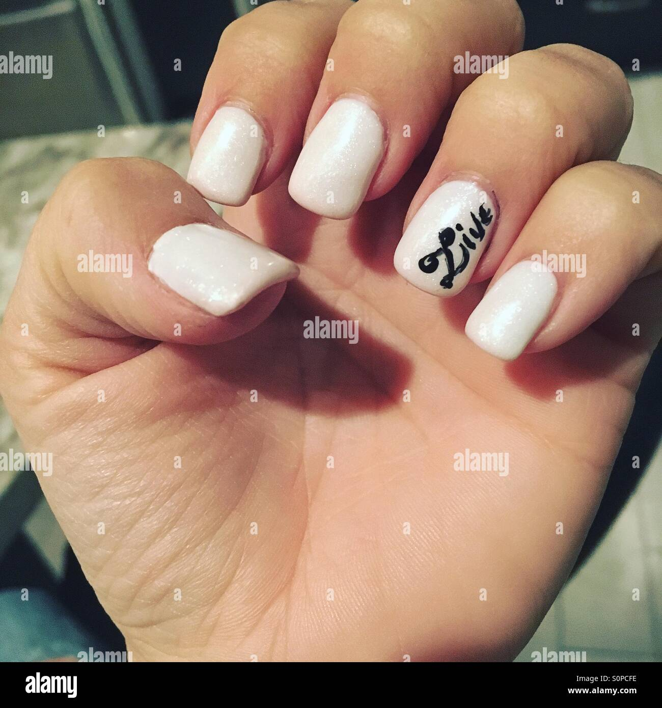 White nails with the word Live on the ring finger Stock