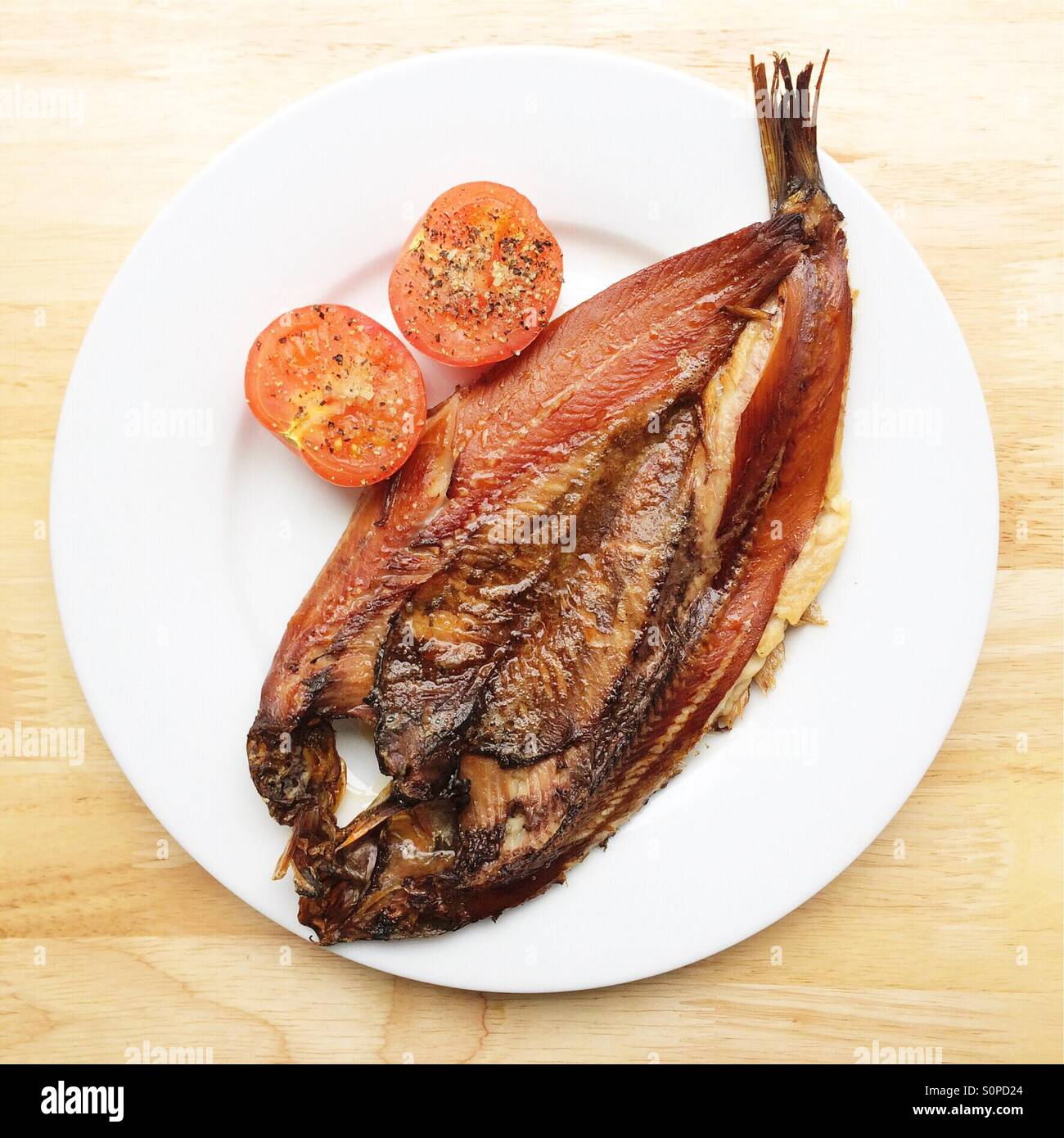 Grilled Kipper with seasoned tomato - Stock Image