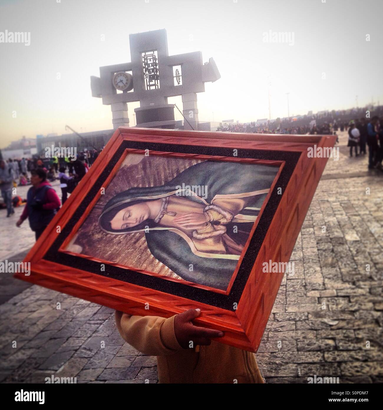 A man carries an image of Our Lady of Guadalupe to be blessed during the pilgrimage to the Basilica of Our Lady - Stock Image