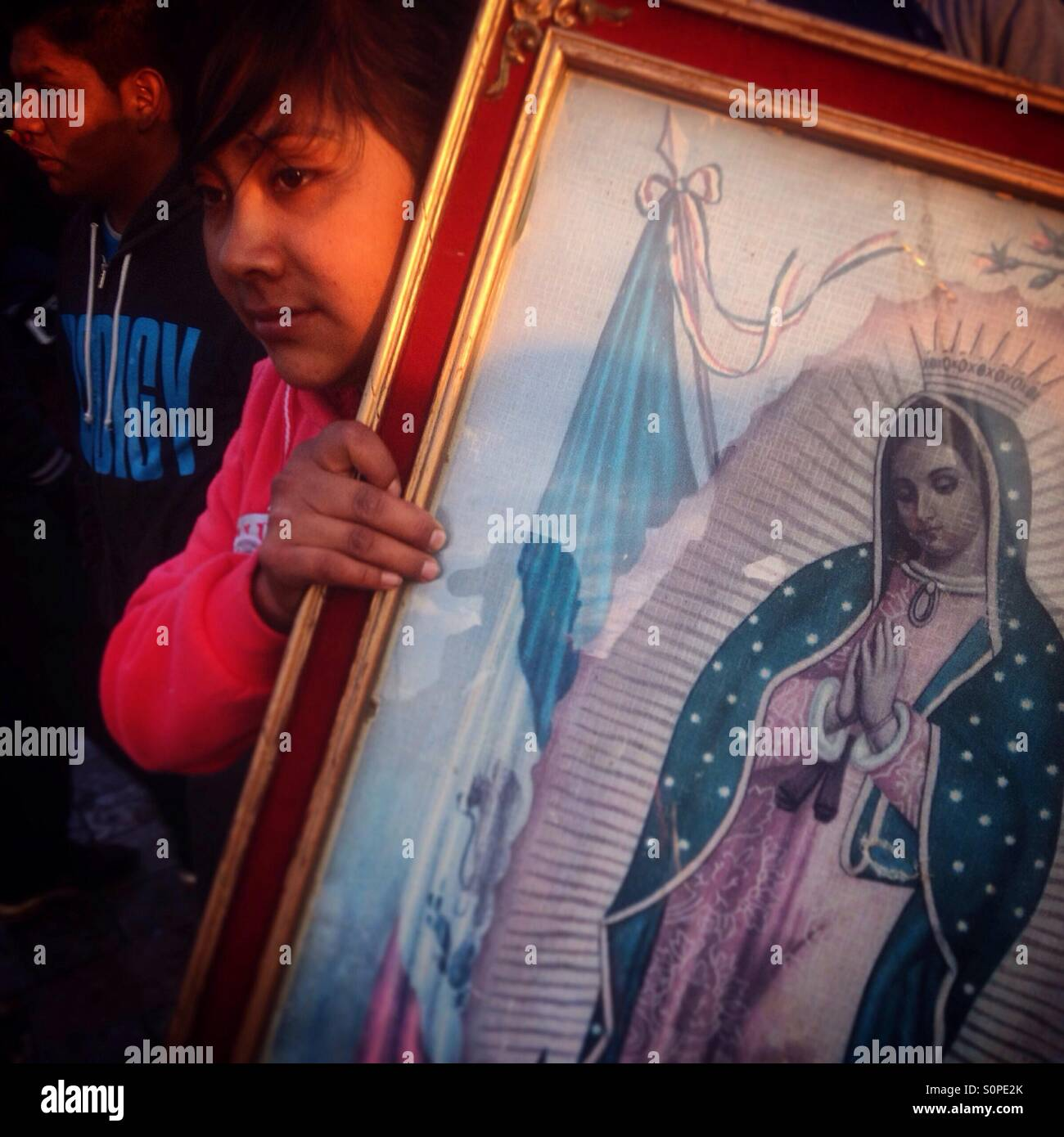 A young pilgrim holds an image of the Virgin of Guadalupe, during the pilgrimage to the Basilica of Our Lady of - Stock Image
