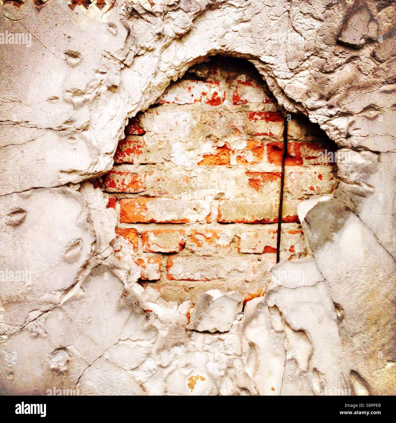 A hole that was created by the impact of a grenade during World War 2 in a wall on a cemetery in Berlin - Stock Image