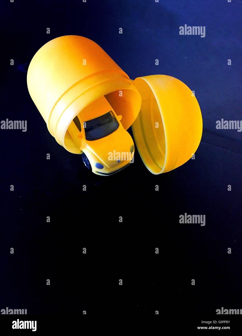 Surprise car toy in egg. Volkswagen car. - Stock Image