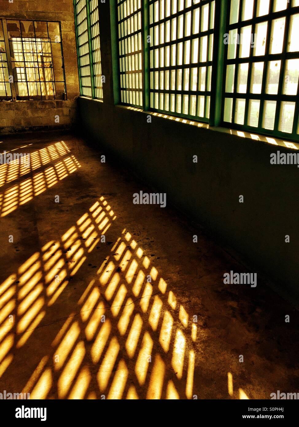 Patterns of light shine through Alcatraz prison windows - Stock Image