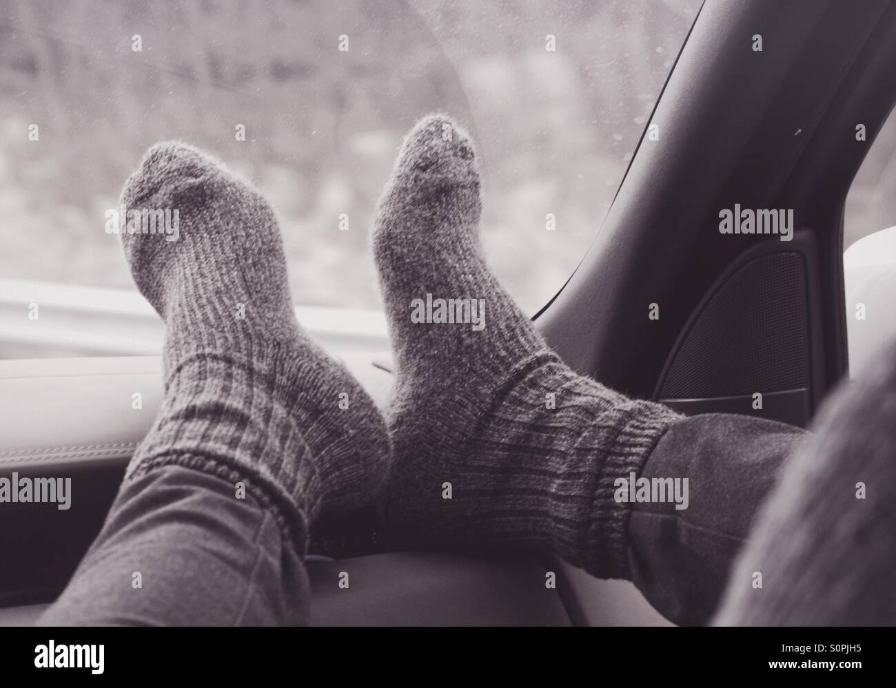 Feet with wool socks on the dash - Stock Image