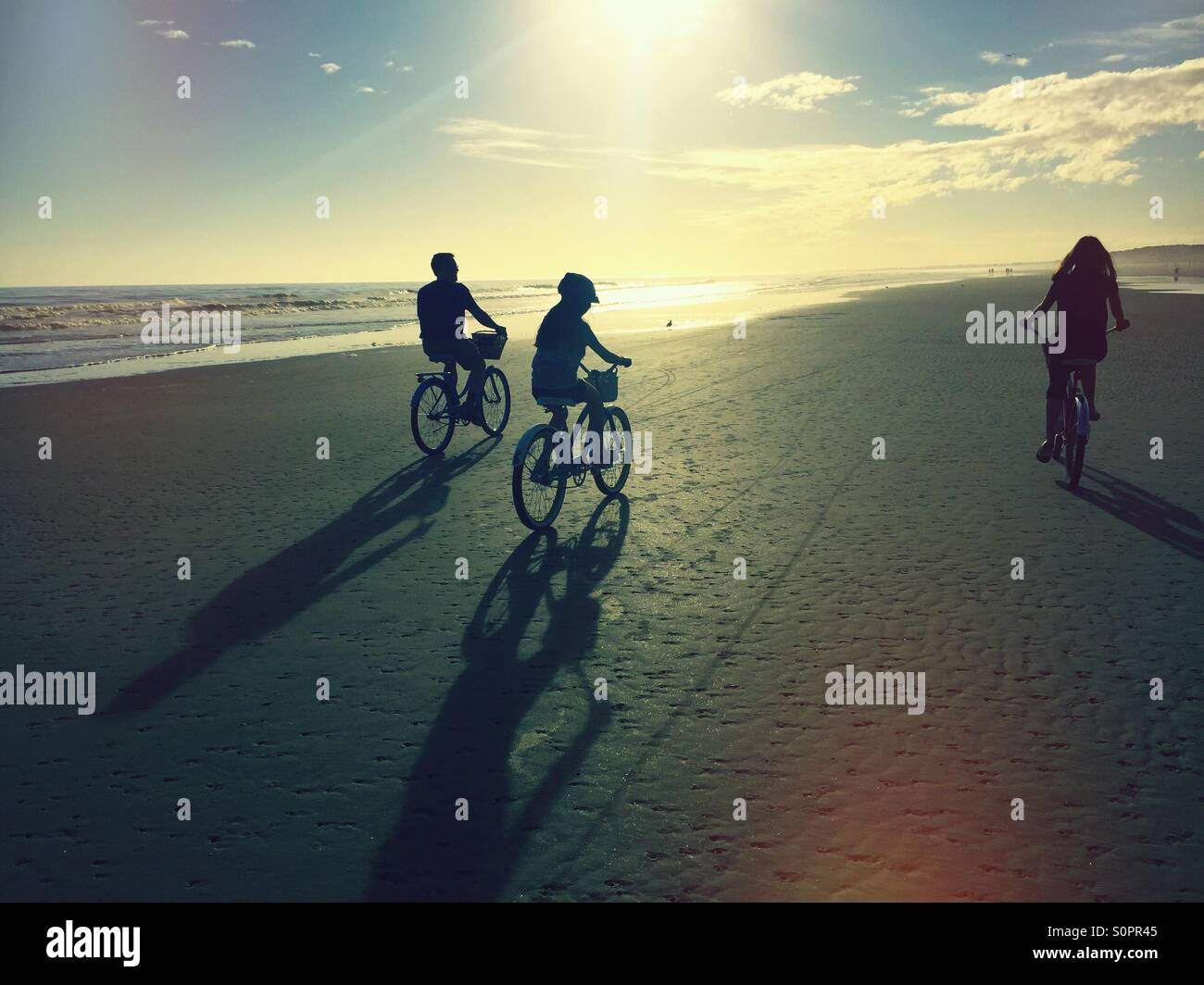 A family bike rides into the sun on the beach at Kiawah Island, SC. They are silhouetted against the sky. - Stock Image