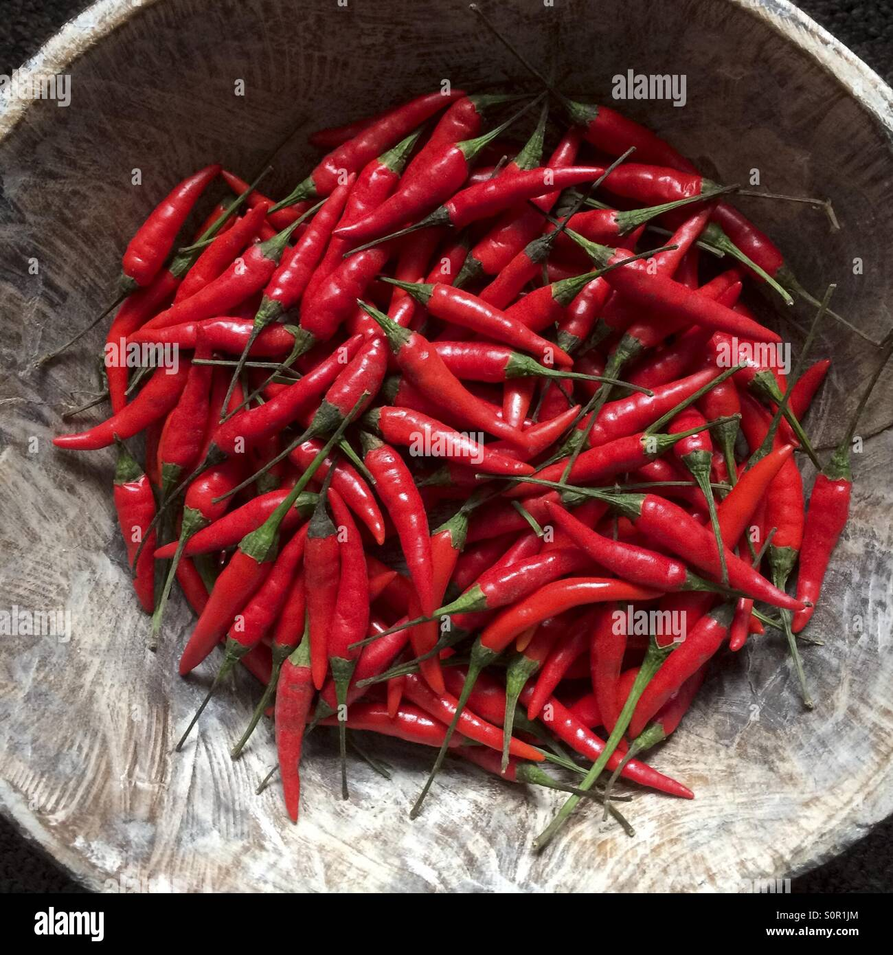 Red Chillies in wooden bowl - Stock Image