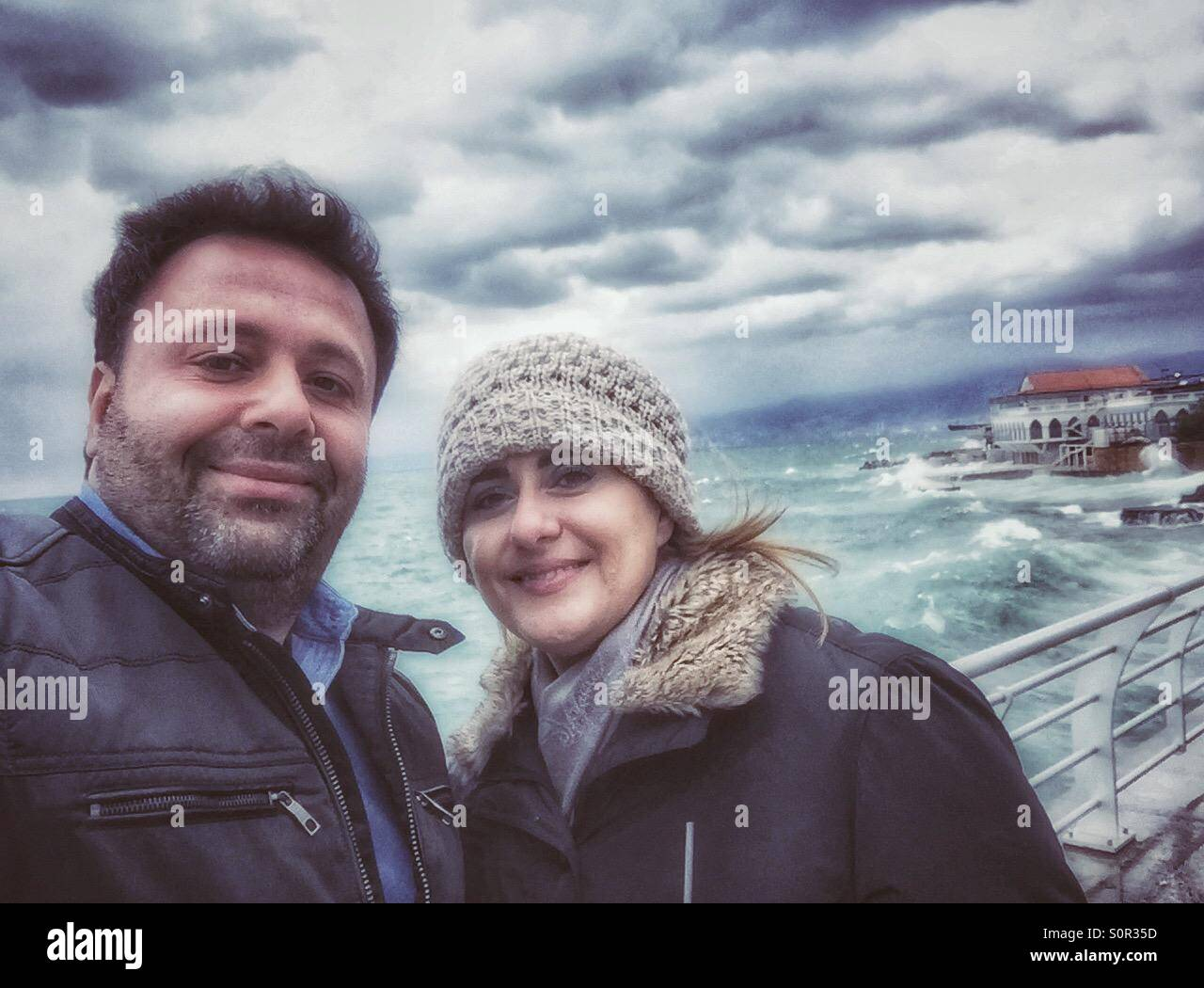 Yong lady ,blonde,coffee,cup of coffee on sea cost,windy day,husseinelsaneh,Mediterranean,crom boarder waves,woman,women.,men,couple,man - Stock Image