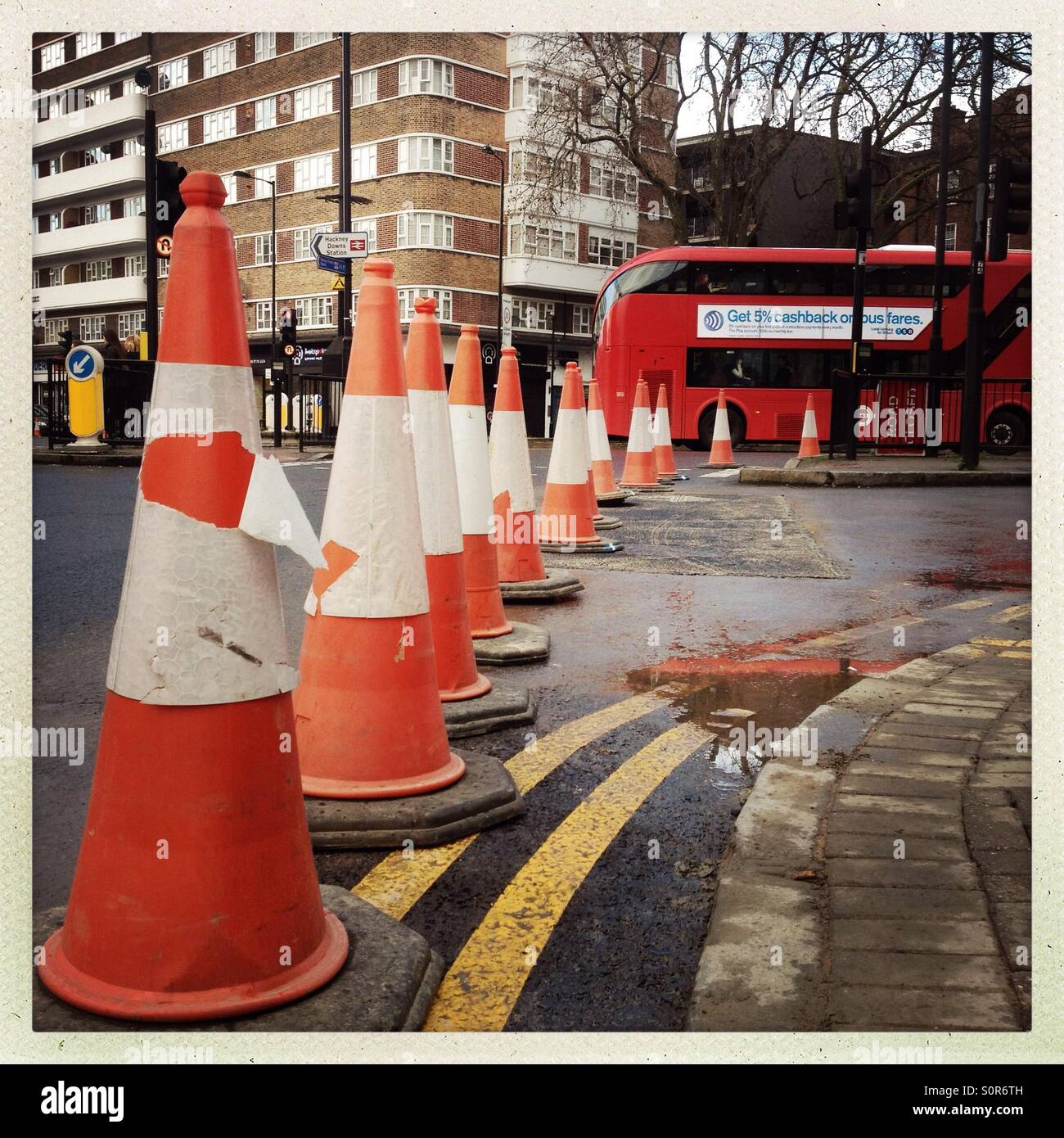 Traffic cones and London double decker bus at pembury Circus in London Hackney east London - Stock Image