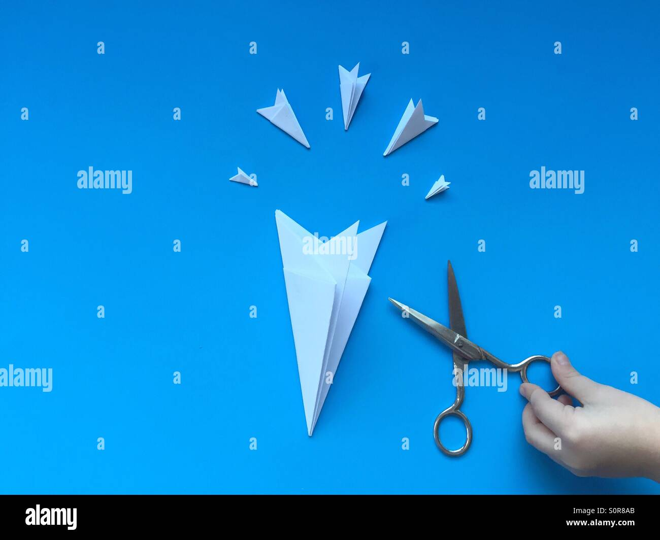 Child prepares to cut paper snowflakes - Stock Image