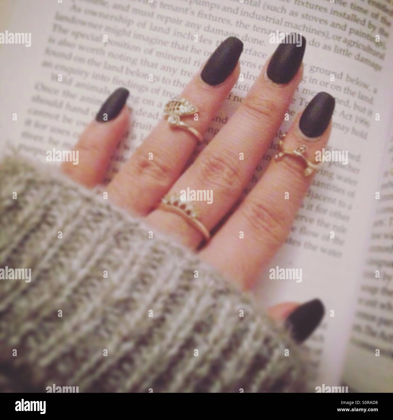 Matte black nails with midi rings in w grey jumper whilst reading a ...
