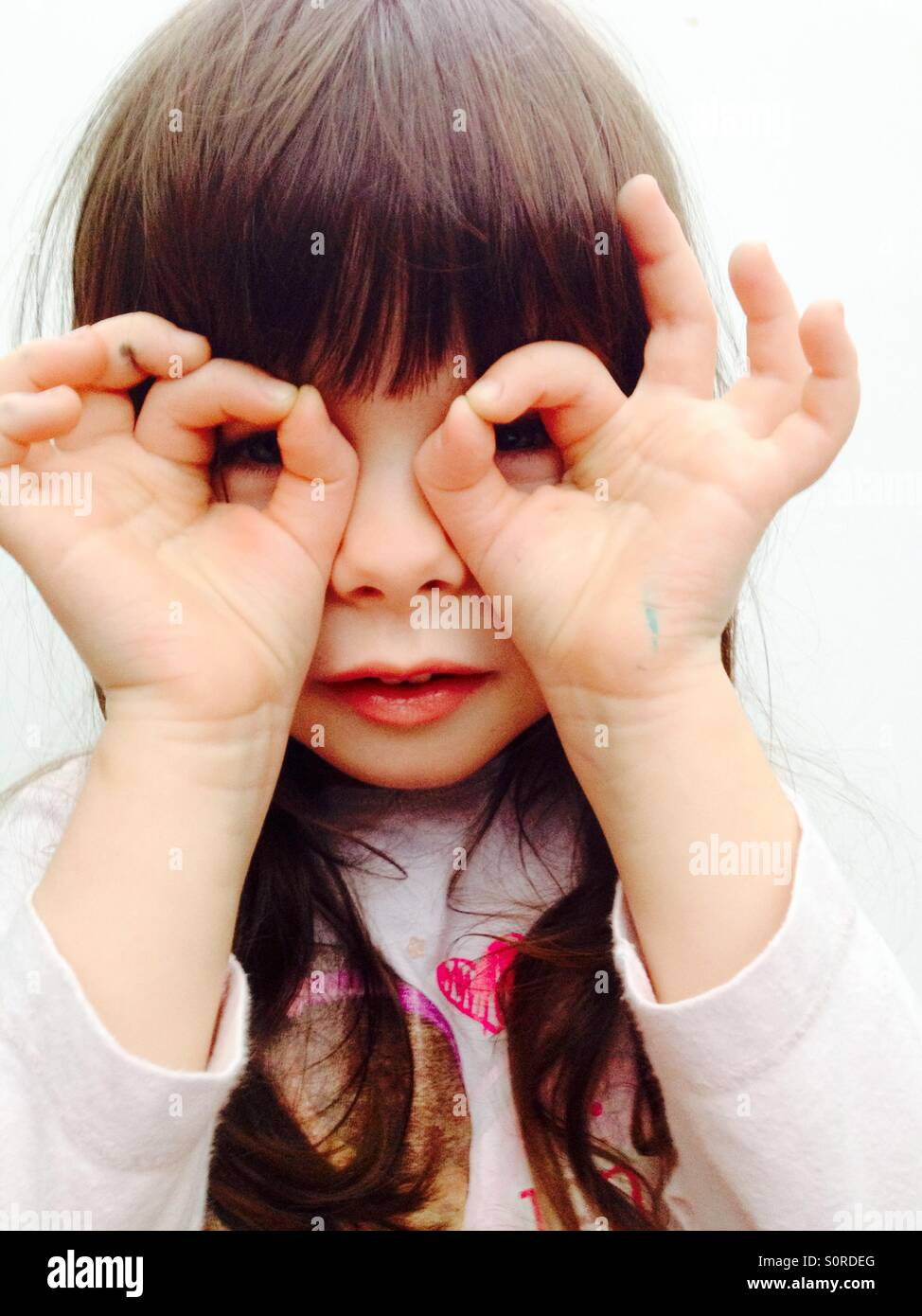 3-year old girl looking though her fingers - Stock Image