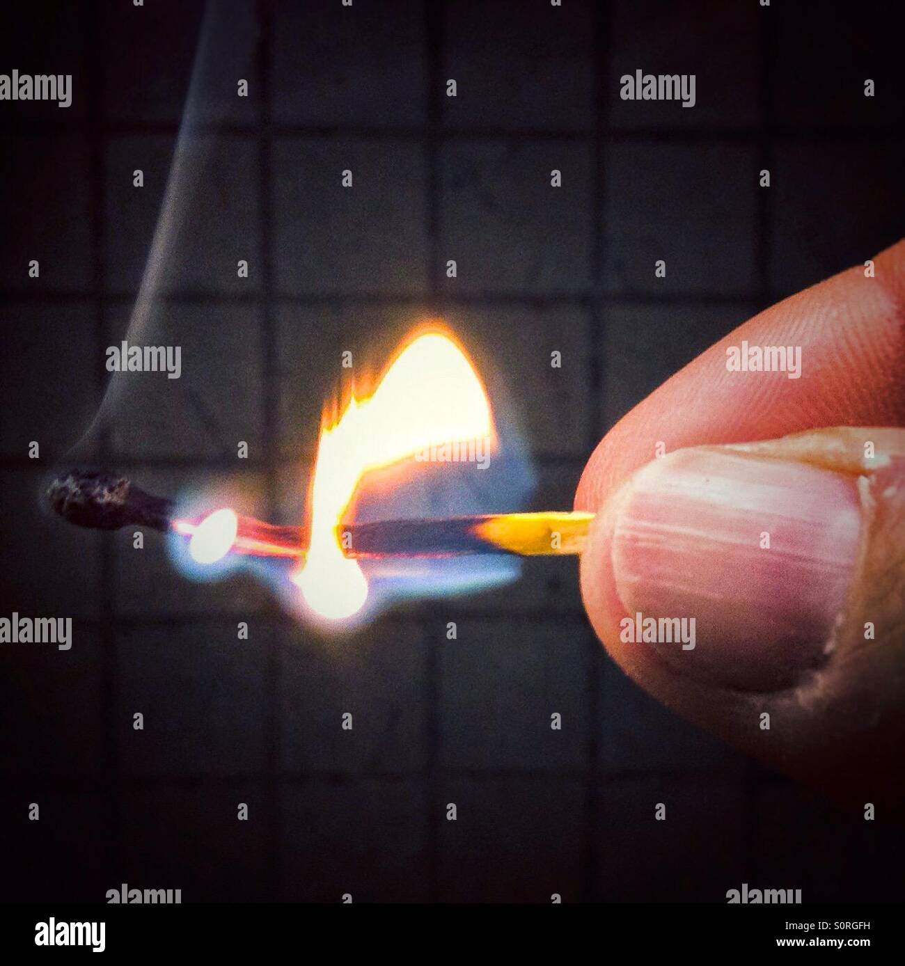 Hand holding burning match stick - Stock Image