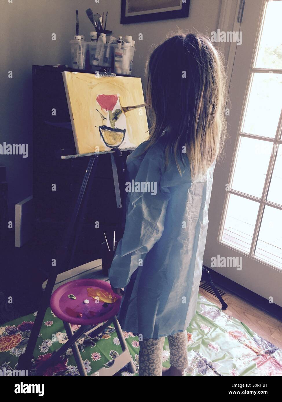 Girl painting a flower - Stock Image