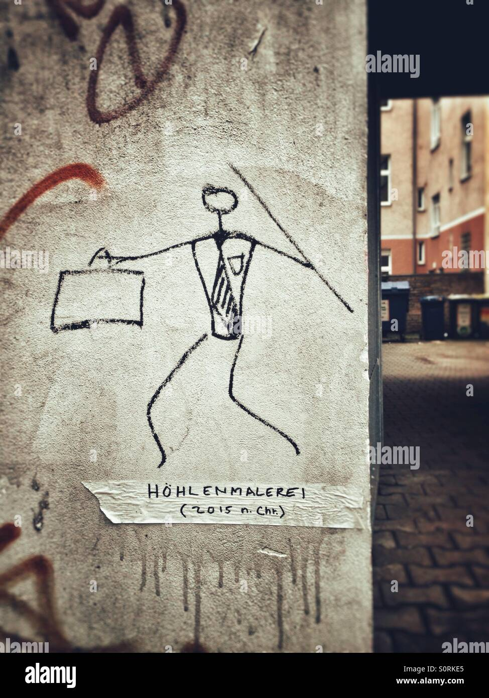Modern caveman on a wall in Berlin, Germany: businessman stickfigure with suit, tie, briefcase and spear; German - Stock Image