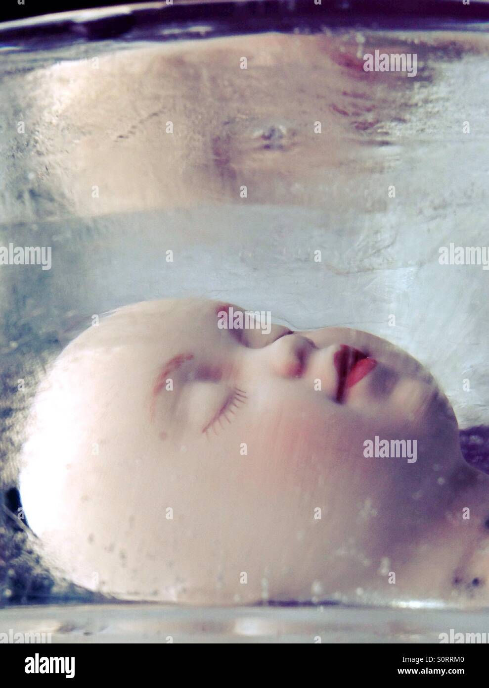 A creepy doll head frozen in ice. - Stock Image