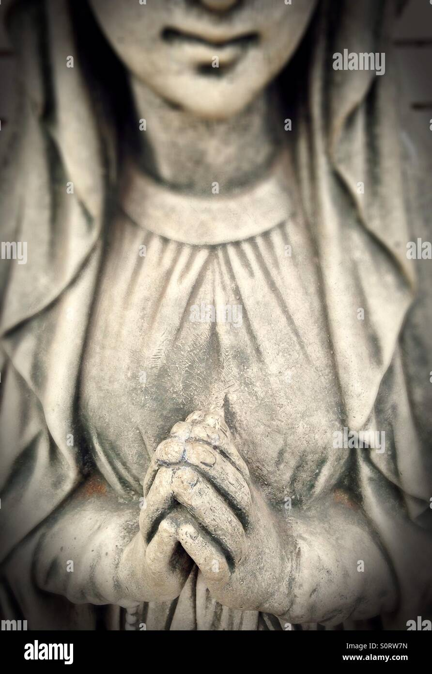 A statue of a woman with hands folded in prayer. - Stock Image