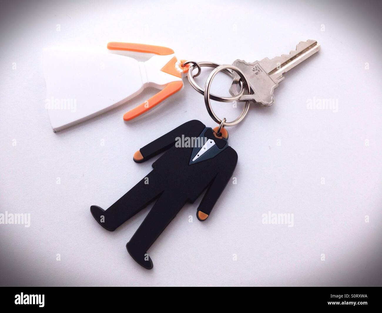Key rings in the shape of a bride and groom sharing one single key. - Stock Image
